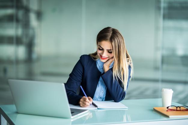 mulher jovem e bonita trabalhando com um laptop e fazendo anotacoes em uma area de trabalho no escritorio 231208 5894